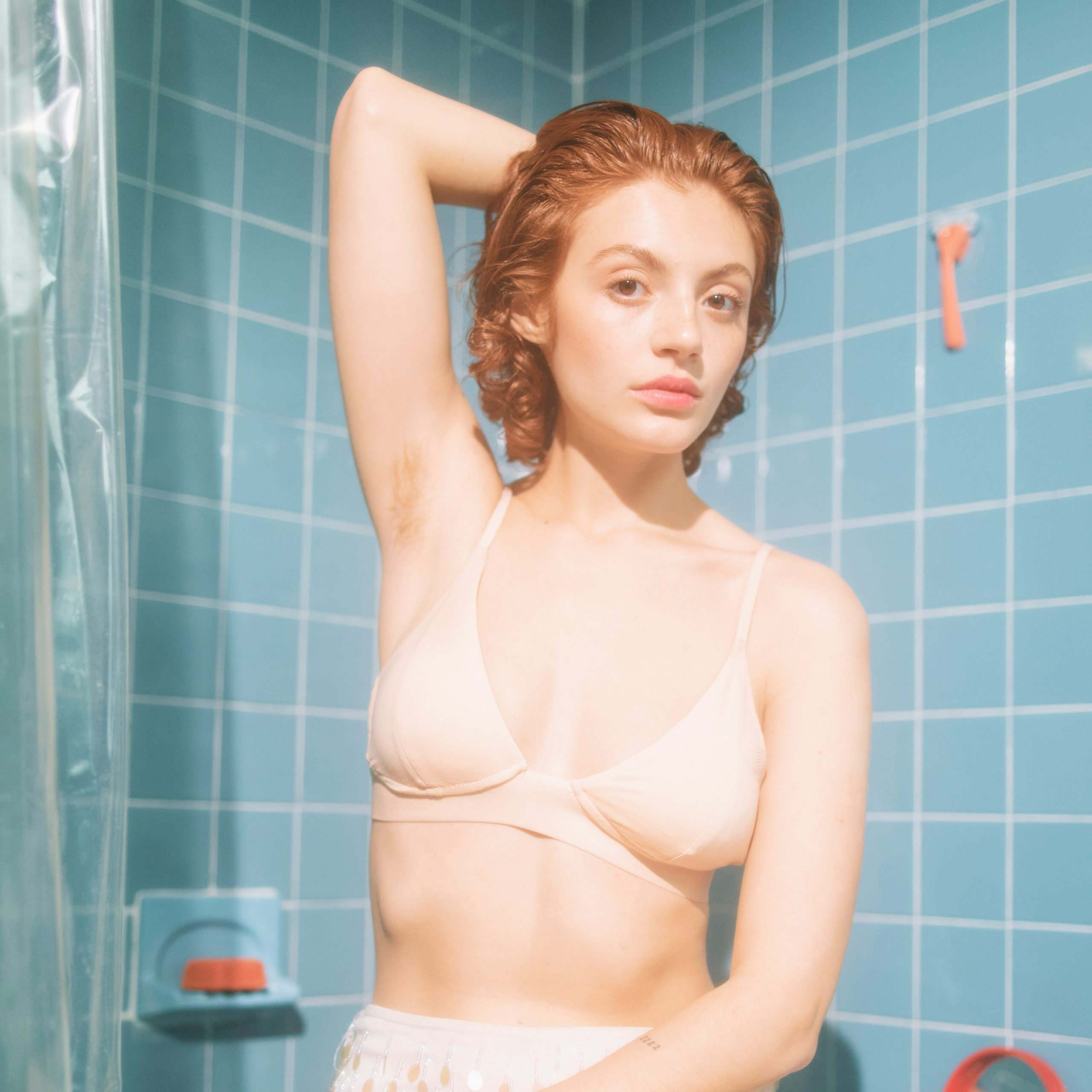 woman in blue shower raising her arm to show hairy armpit